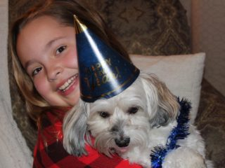 Child holding Shih Tzu wearing New in years eve hat